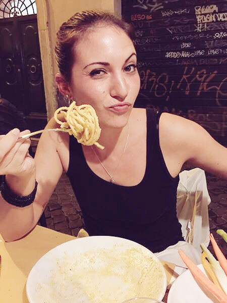 brunette woman eating pasta in Rome Italy