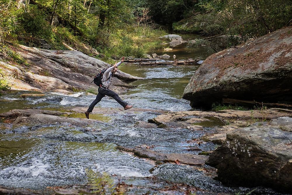 man jumping across rocks in a mountain creek