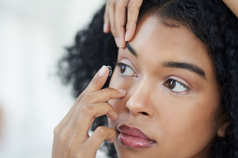 A patient putting in her contact lens.