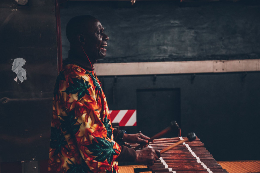 African man playing instrument in authentic African clothing