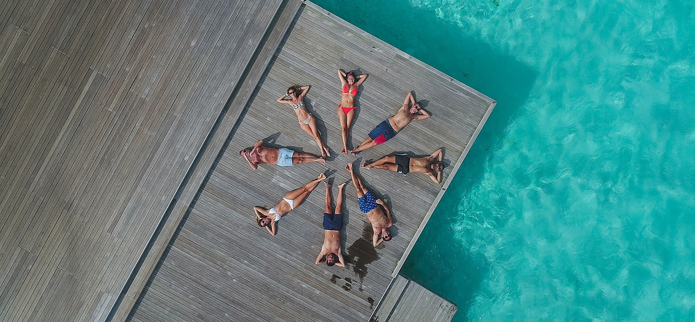 aerial image of group of sun bathers on a dock