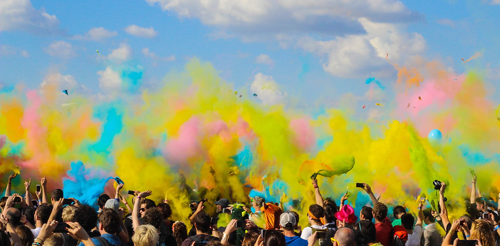 crowd at festival with colorful powder in the air