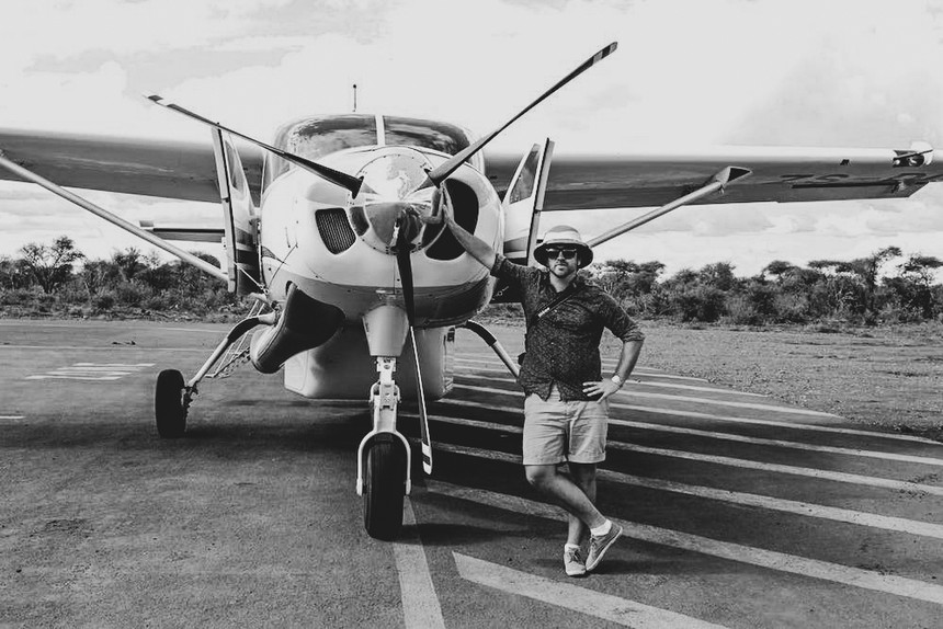 black and white image of Ketil with a small private plane on runway
