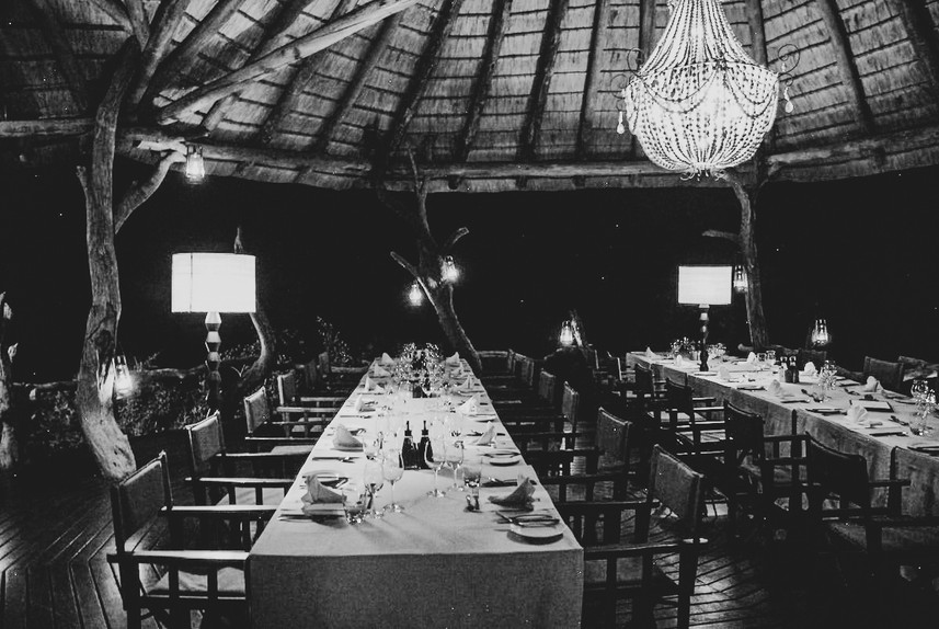 black and white image of dinner set up in a safari resort hut