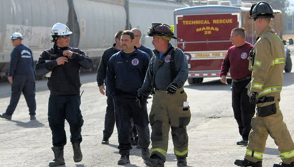 Firefighters walking next to a freight train