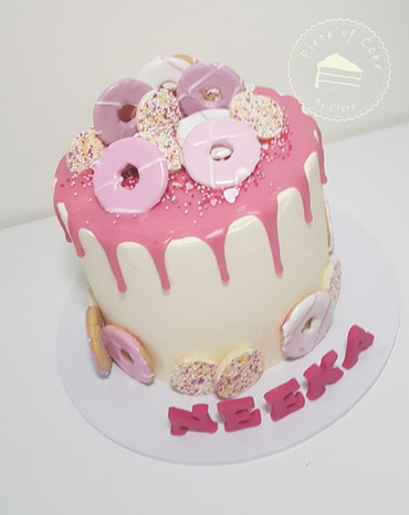 Pink drip cake with party rings and jazzies