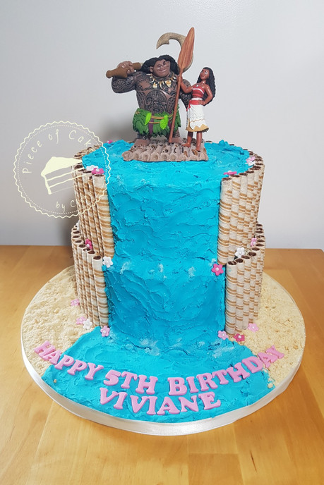 Moana cake.  A vanilla rainbow layer sponge filled with a delicous buttercream.  The edges are covered with Askey's Chocolatey Cafe Curls.  The sand is made from Nice biscuits and the waterfull is blue buttercream.  Maui and Moana stand proudly on a raft made from fondant.
