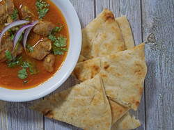 Lamb curry with pita bread utensils