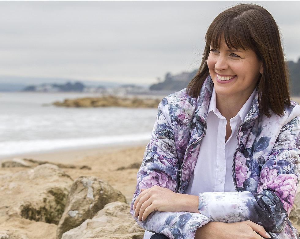 Model sittin on the beach wearing  BPR (big pink rose) hooded jacket