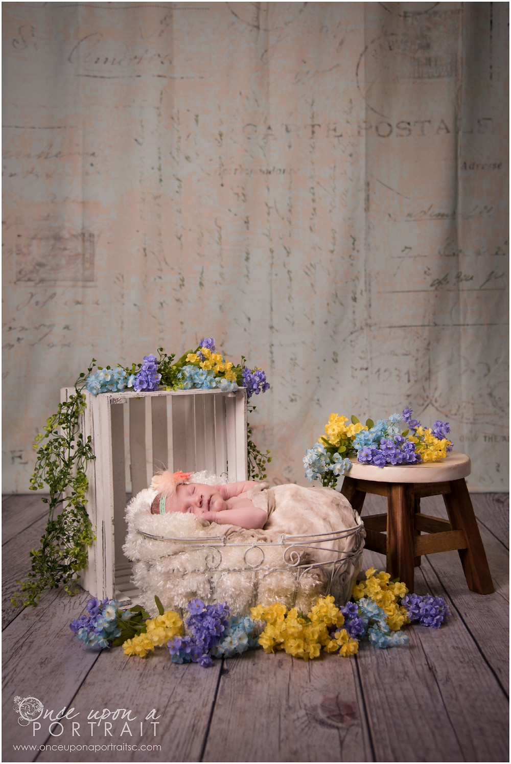 Newborn baby girl with headband and flowers in studio in Simpsonville South Carolina