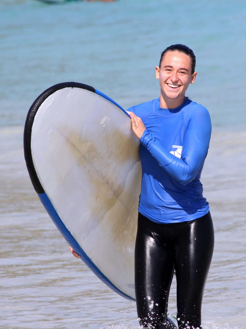 A smiling guest from Kura Kura Surf Camp holding a soft top
