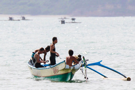 Japanese surfers on a local Indonesian fishing boat