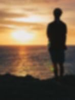 A male watching the sunset while enjoying Bintang beer