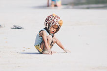A kid playing with sand on the beach