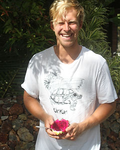Manager of Kura Kura Surf Camp holding a half eaten dragon fruit