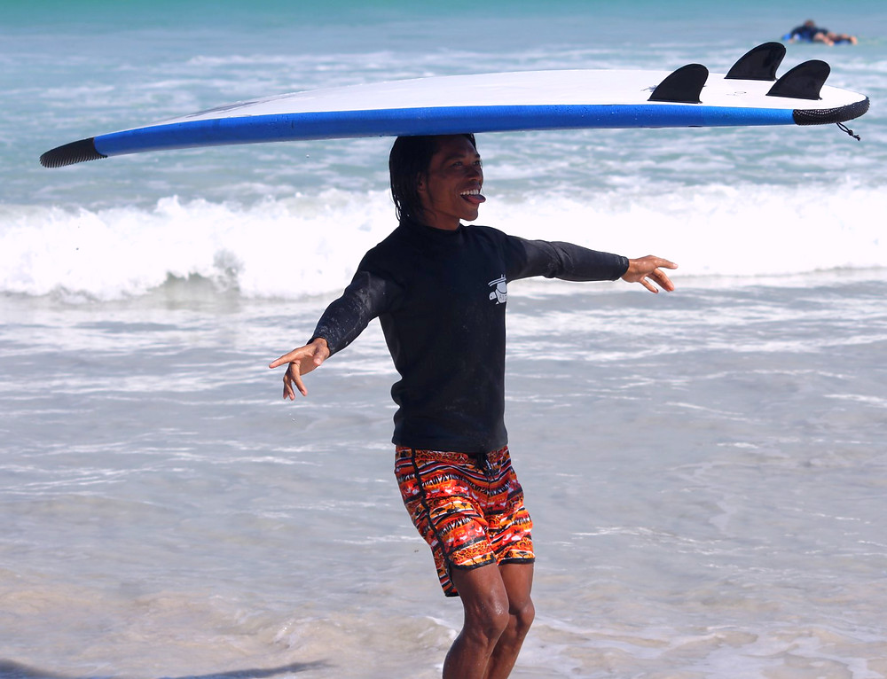 A lombok surfer balancing a surf board on his head