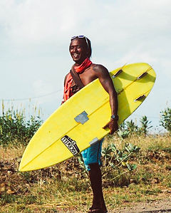 Surf guide carrying his bright yellow shortboard