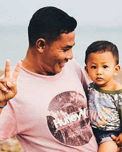 Sasak man posing a peace sign while carrying his toddler son