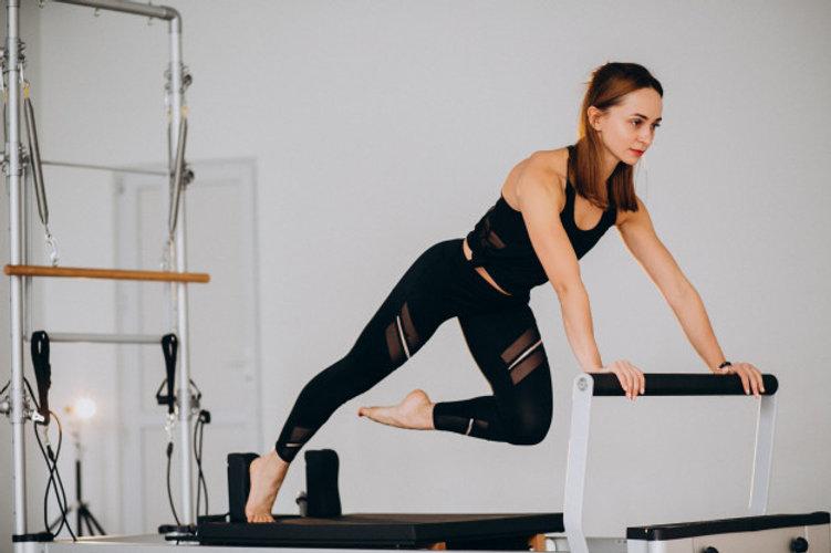 mulher-fazendo-pilates-em-um-reformador_