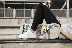 pov of a female skater holding a skateboard between her feet