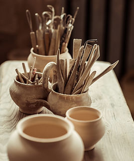 Close up of paint brushes with pottery tools in bowls on table.jpg