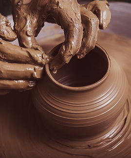 Woman hands working on pottery wheel and making a pot..jpg