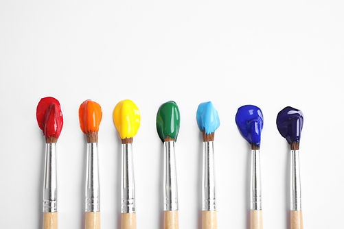 Brushes with bright paints on white back