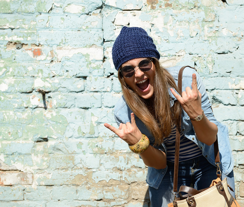 portrait of beautiful cool girl gesturing in hat and sunglasses over grunge wall.jpg