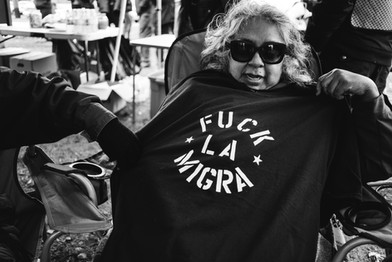 """A woman shows off her """"Fuck la Migra"""" t-shirt at the People's Tribunal at the Northwest Detention Center – the largest migrant detention center in the Pacific Northwest where thousands of migrants are imprisoned and numerous human rights violations are committed against them every day.. These shirts were created by a graphic artist who works with Community 2 Community and Familias Unidas por la Justicia, organizations based in Bellingham, WA, which support  migrant farmworkers and their families in Washington State. Tacoma, Washington February 2018"""