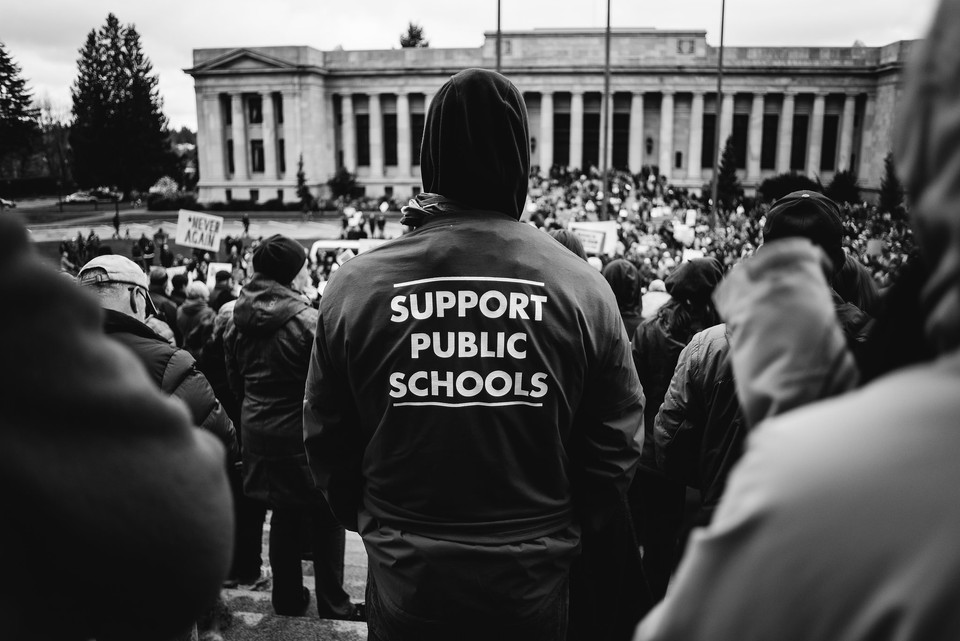 """A man wears his """"support public schools"""" t-shirt to the March for Our Lives rally."""