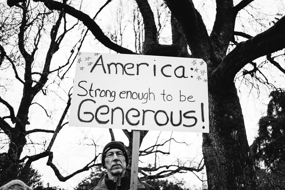 A man advocates for generosity at the Women's March.