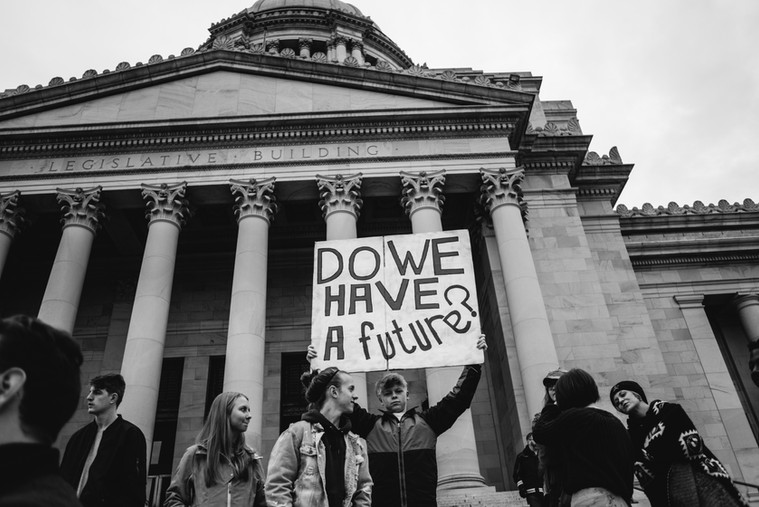 Youth activists and adult supporters gather on the steps of the Washington State Capitol Building to demand immediate Climate Action.