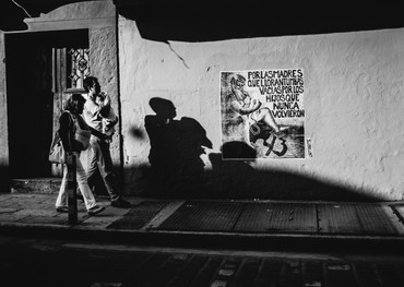 A young couple with a new baby walk past an artistic political message honoring the mothers of the 43 students from Ayotzinapa, Guerrero, who were disappeared in late September of 2014. The students were headed to Mexico City to participate in the annual march commemorating the October 2, 1968 student massacre of Tlatelolco. Justice for the students has not been achieved: the case, like the majority regarding disappearances and assassinations in México, remains with complete impunity. According to a citizen from the City of Mexico, Mexico has had this problem of impunity and lack of human sentimentality towards its population forever. The student murders show the extent of systematic oppression and lack of free expression in Mexico; those who express themselves freely are reprimanded by the system, silenced, assassinated. To be a student is not to be a criminal.  Oaxaca de Juárez, Oaxaca  November 2017