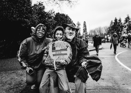 A young boy sits on the knee of his disabled* father, with his mother at his side, at the National March for Our Lives at the Washington State Capitol Building.      *divergent Olympia, Washington March 2018