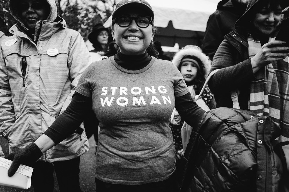"""A woman shows off her """"strong woman"""" t-shirt at the Women's March."""