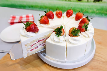 a cut of cake with whipped cream and str