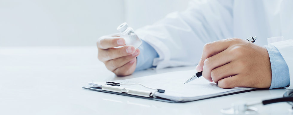 doctor with a medicine bottle in one hand, and a pen in the other hand, writing on a paper