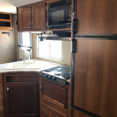 Avenger 2: Kitchenette with double sink, 3 range stove/oven combo, Microwave, stove vent, and midsize fridge with freezer on top