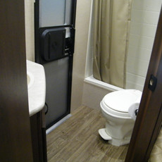 White Hawk: Bathroom with toilet, sink, and shower. Features a second entry for easy access when hanging out outside the camper.