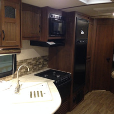 White Hawk: Kitchenette with double sink, 3 range stove/oven combo, Microwave/vent combo, Mid-size fridge with freezer on top.