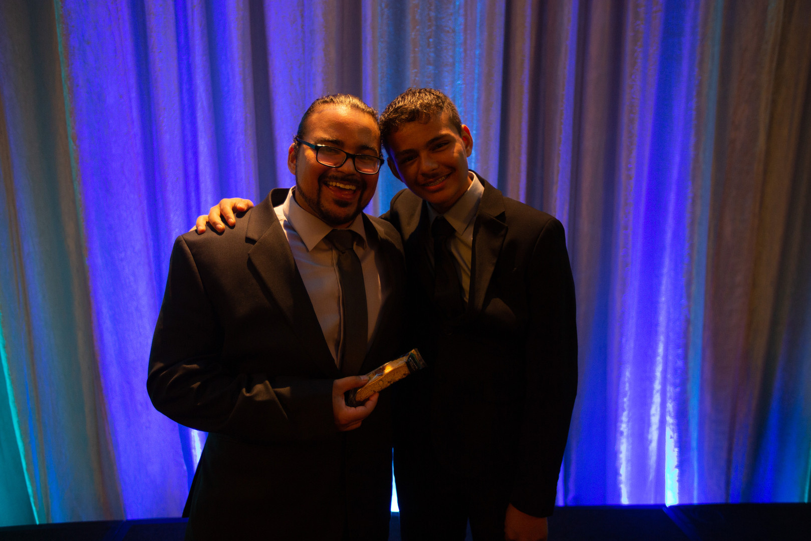 Father and son smiling and holding award