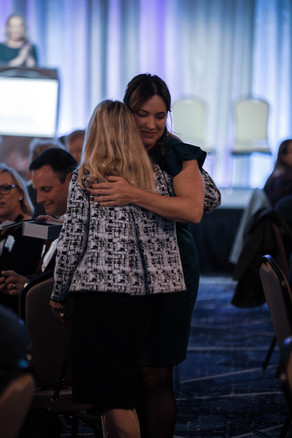 Two women hugging at the Ryther luncheon