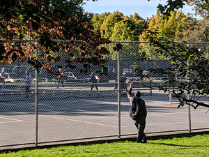 Man standing behind fence watchin people play basketball