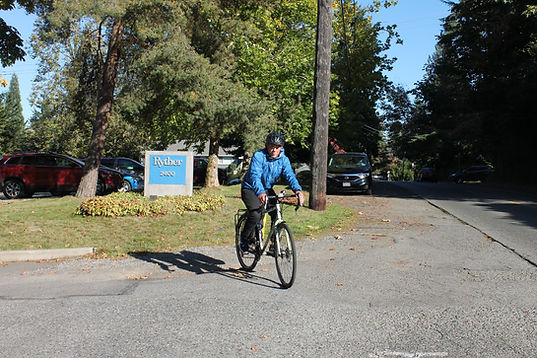Substance Use Therapist riding bike in front of Ryther sign