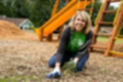 Smiling female volunteer pulling weeds on a playground