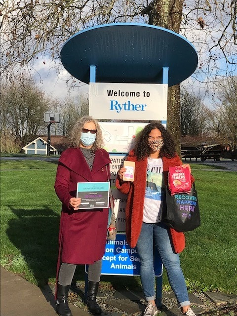 """Miranda (right) outdoors in a mask and a bright red coat in front of a Ryther sign holding care package items and a tote bag that says """"Recovery Happens Here"""", with KCRC's Director, Heather (left) in a dark red coat, masked, holding an appreciation certificate."""