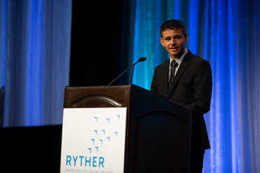Boy giving speech at Ryther luncheon behind a podium