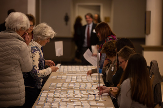 Volunteers helping group of women find their nametags at the Ryther luncheon