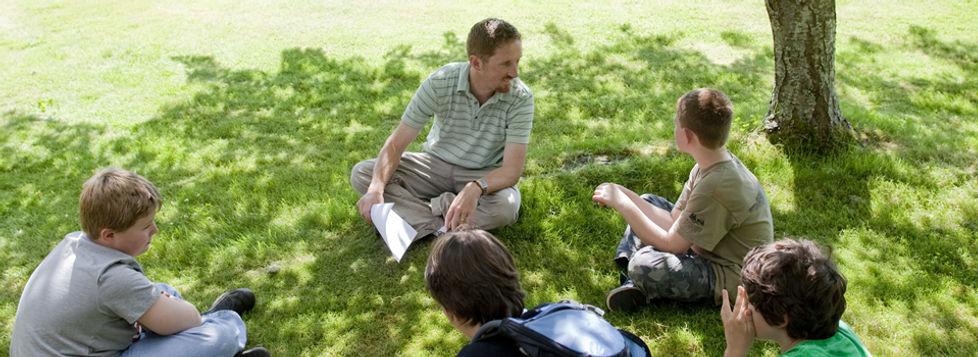 Man sitting in a circle talking to four boys