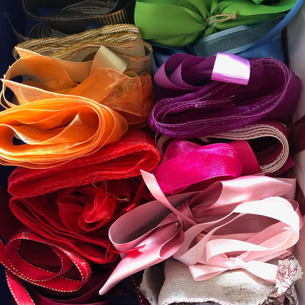 A decluttered and organised collection of ribbons in rainbow.